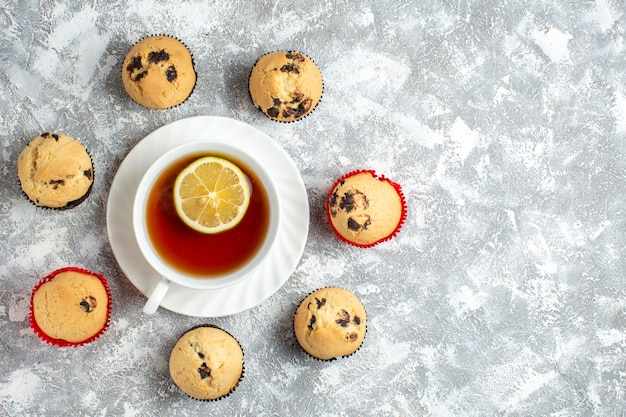 Boven weergave van heerlijke kleine cupcakes met chocolade rond een kopje zwarte thee aan de rechterkant op ijsoppervlak