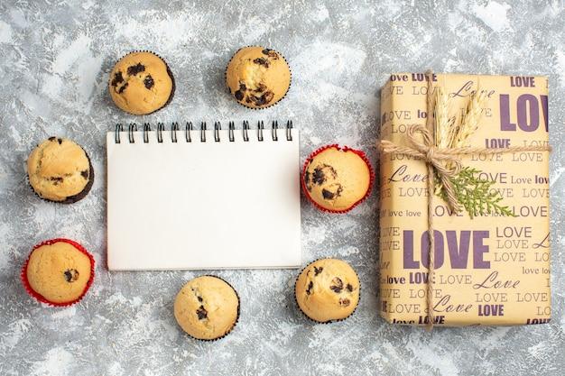Boven weergave van heerlijke kleine cupcakes met chocolade rond notitieboekje en cadeau met liefdesinscriptie op ijsoppervlak