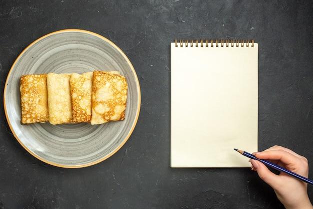 Boven weergave van heerlijke met vlees gevulde pannenkoeken op een witte plaat en notitieboekje op zwarte achtergrond