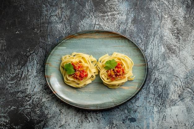 Boven weergave van heerlijke pastamaaltijd met tomatenvlees en groen op een blauw bord op ijsachtergrond