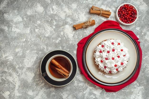 Boven weergave van heerlijke romige cake versierd met fruit op een rode doek