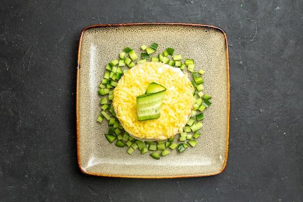 Boven weergave van heerlijke salade geserveerd met gehakte komkommer op donkere achtergrond