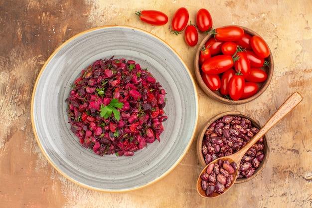 Boven weergave van heerlijke salade met rode biet en bonen en bonen binnen en buiten pot en tomaten op gemengde kleurentafel