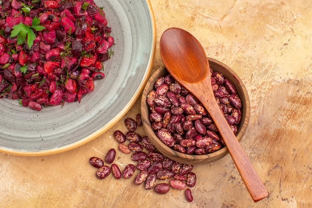 Boven weergave van heerlijke salade met rode biet en bonen en bonen binnen en buiten pot op gemengde kleur achtergrond