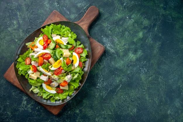 Boven weergave van heerlijke salade met veel verse ingrediënten aan de rechterkant op houten snijplank op zwart groen mix kleuren tafel