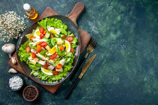 Boven weergave van heerlijke salade met veel verse ingrediënten op houten snijden boa rd specerijen oliefles bestek aan de rechterkant op zwarte groene mix kleuren tafel
