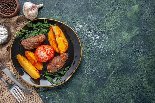 Boven weergave van heerlijke vleeskoteletten gebakken met aardappelen en tomaten op een zwarte plaat kruiden knoflook bestek aan de rechterkant op groen zwart mix kleuren achtergrond