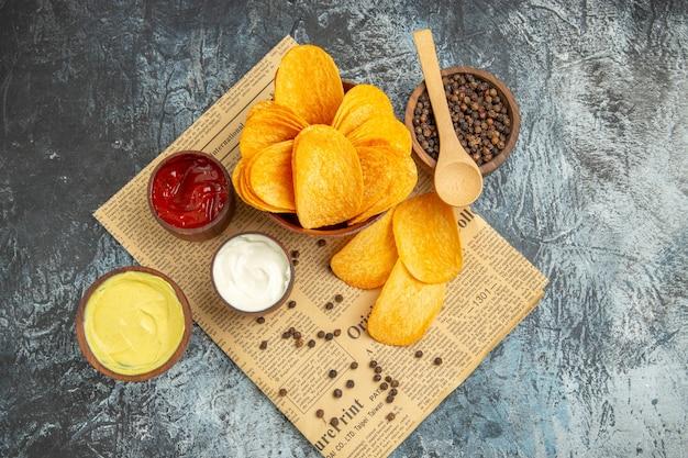 Boven weergave van heerlijke zelfgemaakte chips en peper kom mayonaise ketchup en saus met lepel op krant op grijze tafel