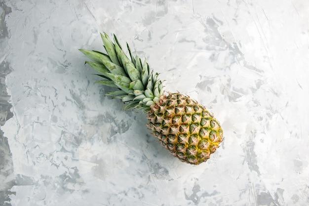 Boven weergave van hele verse gouden ananas op marmeren oppervlak