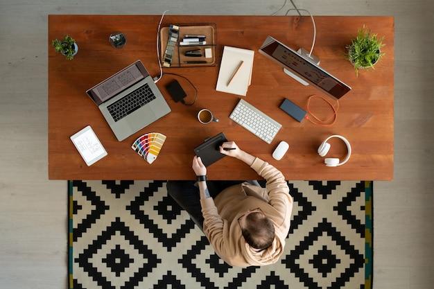 Boven weergave van interface-ontwerper in hoodie zittend aan een houten bureau vol met apparaten en schets puttend uit digitizer tablet