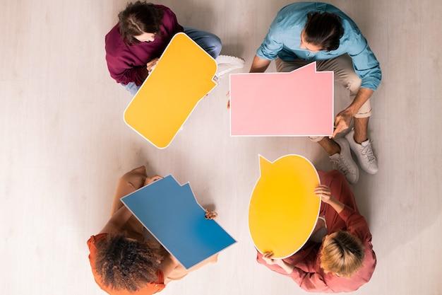 Boven weergave van jonge mensen die in een cirkel zitten en lege tekstballon-tags vasthouden terwijl ze online communiceren
