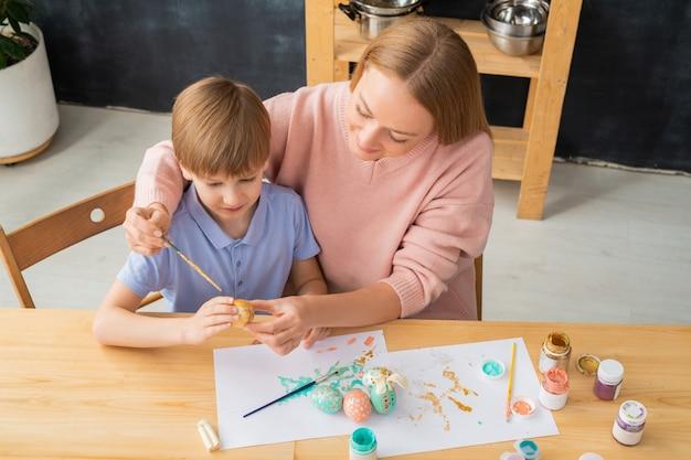 Boven weergave van jonge moeder en zoon zittend aan tafel met kunstgereedschap en paasei schilderen