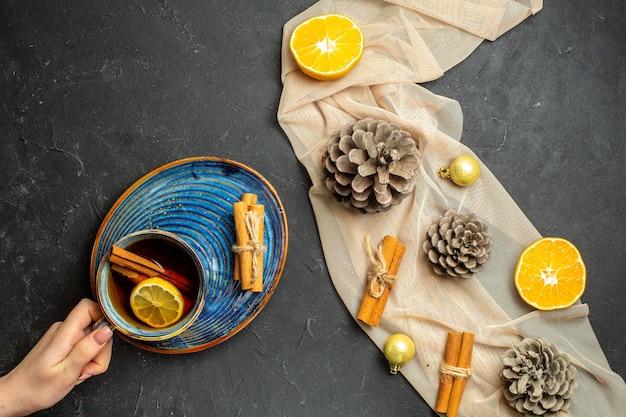 Boven weergave van kaneel limoenen gesneden sinaasappelen en drie coniferen kegels op naakt kleur handdoek een kopje zwarte thee op zwarte kleur achtergrond