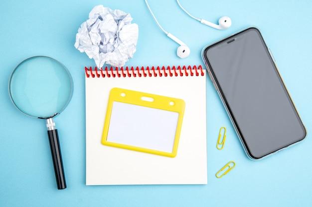 Boven weergave van kantoorconcept met hoofdtelefoon mobiele telefoon spiraal notebook verpletterd papier vergrootglas op blauw oppervlak