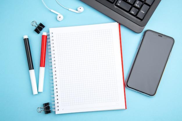 Boven weergave van kantoorconcept met hoofdtelefoon voor mobiele telefoons en spiraalvormig notitieboekje op blauw oppervlak
