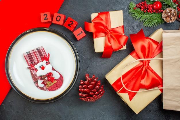 Boven weergave van kerst sok op een plaat naaldboom kegel fir takken nummers mooie geschenken op een donkere tafel