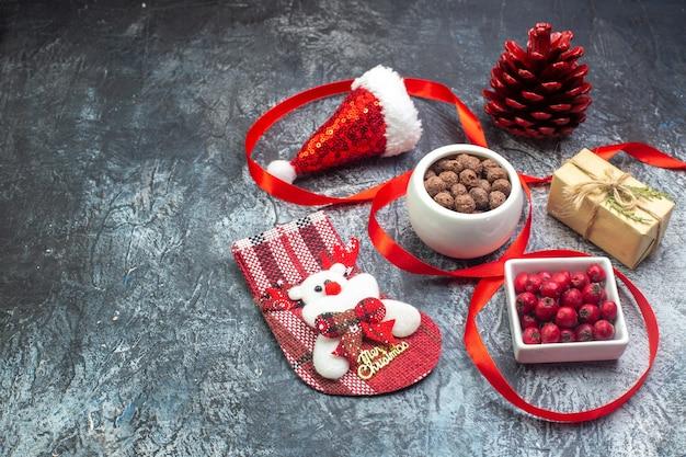 Boven weergave van kerstman hoed en cornel chocolade nieuwjaarssok rode conifer kegel aan de linkerkant op donkere ondergrond