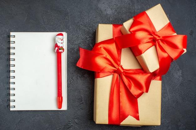 Boven weergave van kerstmis achtergrond met mooie geschenken met boogvormig lint en notitieboekje met pen op een donkere achtergrond