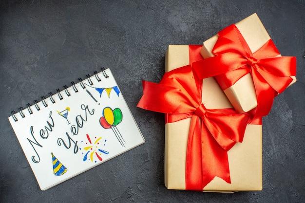 Boven weergave van kerstmis achtergrond met prachtige geschenken met boogvormig lint en notitieboekje met nieuwjaar schrijven op een donkere achtergrond