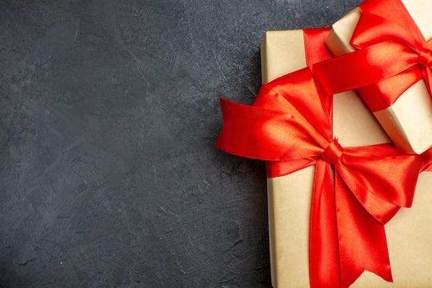 Boven weergave van kerstmis achtergrond met prachtige geschenken met boogvormig lint op een donkere achtergrond