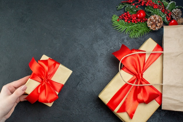 Boven weergave van kerstsfeer met hand met een van de mooie geschenken en fir takken conifer kegel op donkere achtergrond