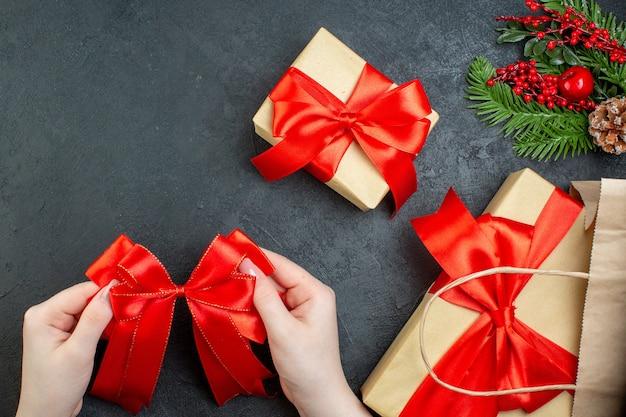 Boven weergave van kerstsfeer met mooie cadeaus en met rood lint op donkere achtergrond