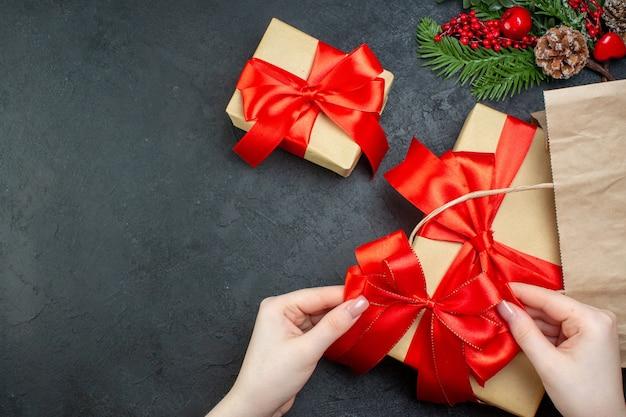Boven weergave van kerstsfeer met mooie cadeaus met rood lint aan de rechterkant op donkere achtergrond