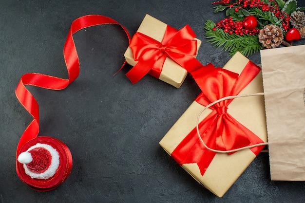 Boven weergave van kerstsfeer met mooie geschenken fir takken conifer kegel rood lint op donkere achtergrond
