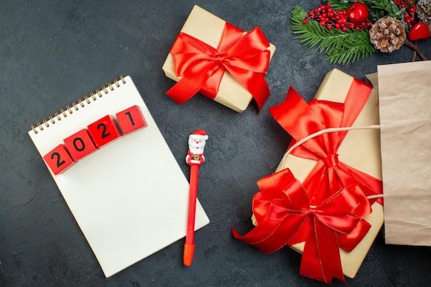 Boven weergave van kerstsfeer met mooie geschenken met rood lint en cijfers op notitieblok met pen op donkere achtergrond