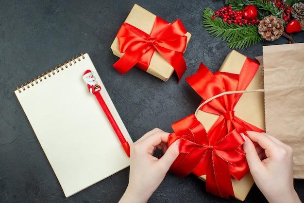 Boven weergave van kerstsfeer met mooie geschenken met rood lint en notitieboekje met pen op donkere achtergrond