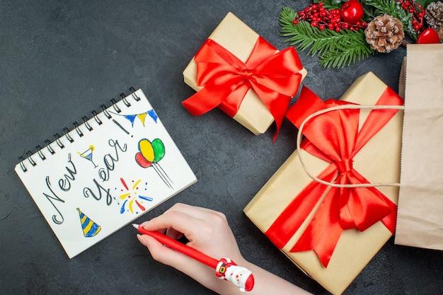 Boven weergave van kerstsfeer met prachtige geschenken en fir takken conifer kegel naast notebook met nieuwjaar tekeningen op donkere achtergrond