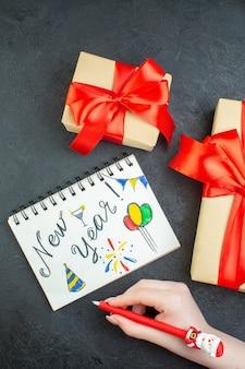 Boven weergave van kerstsfeer met prachtige geschenken en notitieboekje met nieuwjaarstekeningen op donkere achtergrond