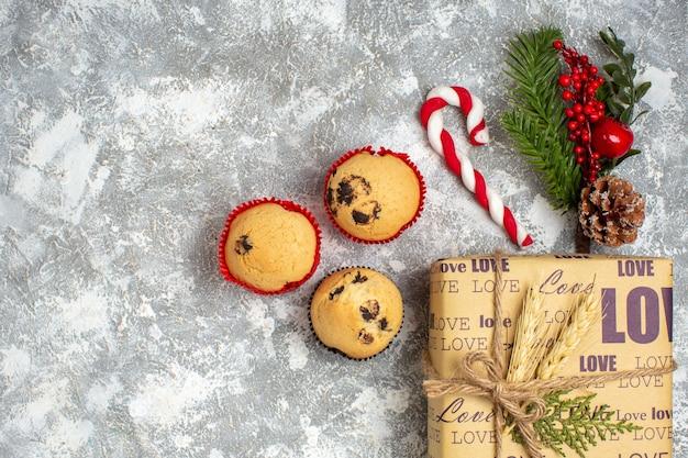 Boven weergave van kleine cupcakes mooi verpakt kerstcadeau met liefdesinscriptie en dennentakken decoratie accessoires conifer kegel aan de linkerkant op ijs oppervlak
