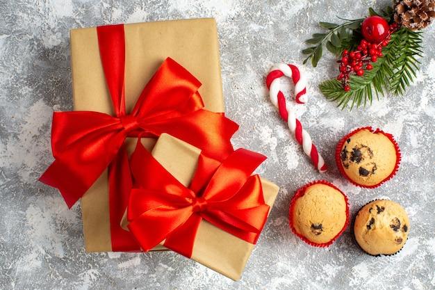 Boven weergave van kleine cupcakes, snoep en dennentakken, decoratieaccessoires en geschenken met rood lint op ijsoppervlak