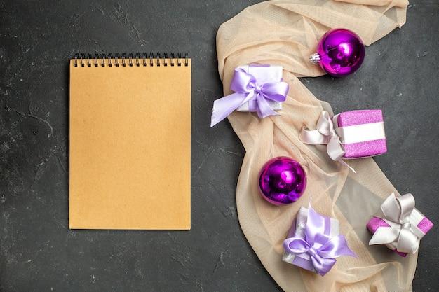 Boven weergave van kleurrijke geschenken decoratie accessoires voor het nieuwe jaar op naakt kleur handdoek en notitieboekje op zwarte achtergrond