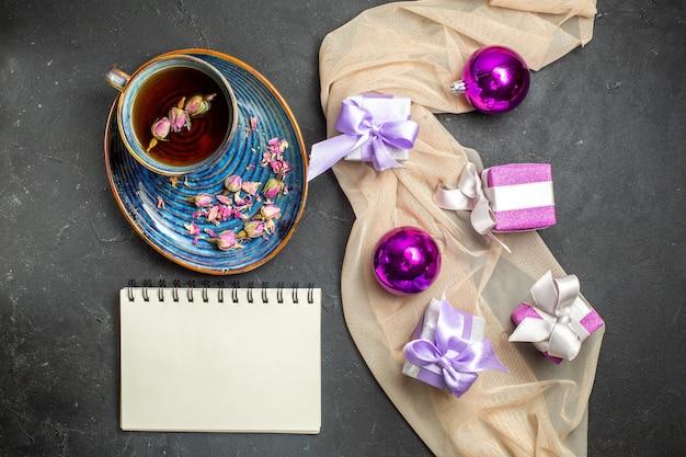 Boven weergave van kleurrijke geschenken decoratie accessoires voor kerstmis op naakt kleur handdoek en een kopje thee naast notebook op zwarte achtergrond