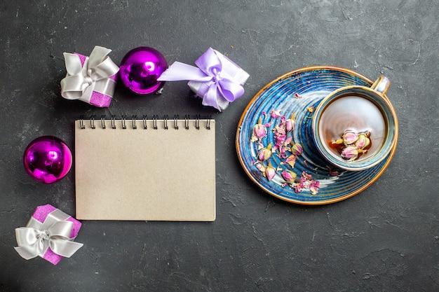 Boven weergave van kleurrijke geschenken en decoratieaccessoires een kopje zwarte thee naast notebook op donkere achtergrond