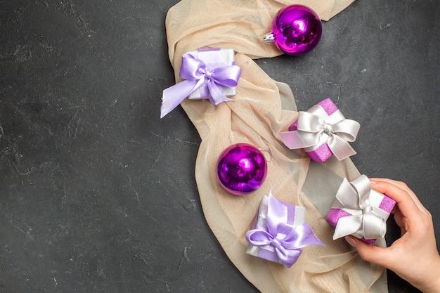 Boven weergave van kleurrijke geschenken en decoratieaccessoires voor het nieuwe jaar op een nudekleurige handdoek op zwarte achtergrond