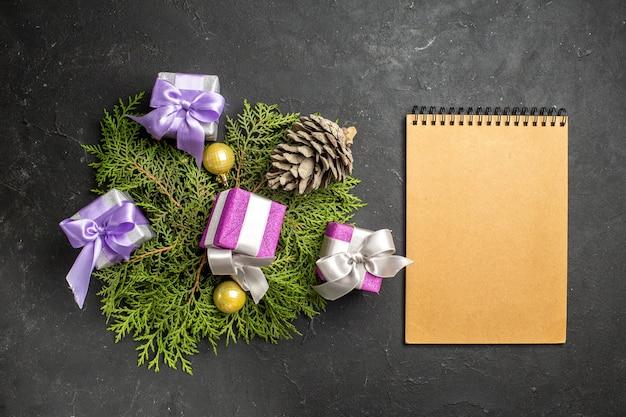 Boven weergave van kleurrijke nieuwjaarsgeschenken decoratie-accessoire en coniferenkegel naast notebook op donkere achtergrond