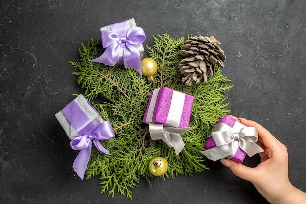 Boven weergave van kleurrijke nieuwjaarsgeschenken decoratie-accessoire en coniferenkegel op donkere achtergrond