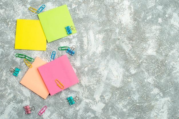 Boven weergave van kleurrijke notitiepapieren en andere kantoorapparatuur op grijze achtergrond