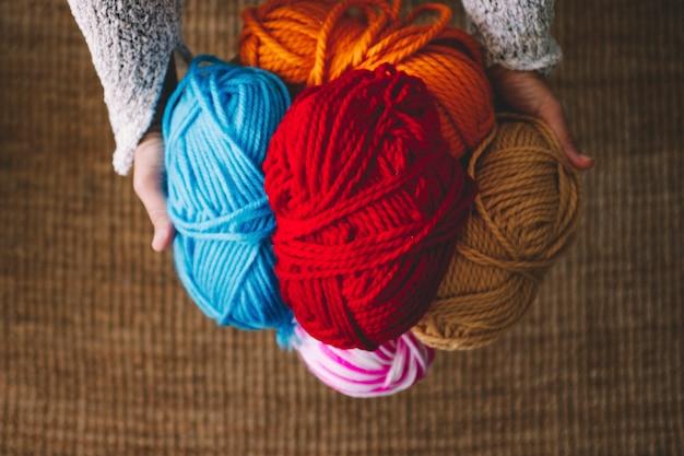 Boven weergave van kleurrijke warme wol vastgehouden door vrouw. thuis vrijetijdsbesteding breiwerk en mensen breien. hobby- en werkconcept