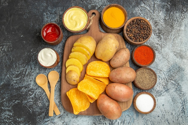 Boven weergave van knapperige chips en ongekookte aardappelen op houten snijplank en verschillende kruiden mayonaise ketchup op grijze tafel