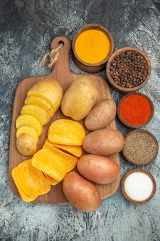 Boven weergave van knapperige chips en ongekookte aardappelen op houten snijplank en verschillende kruiden op grijze tafel