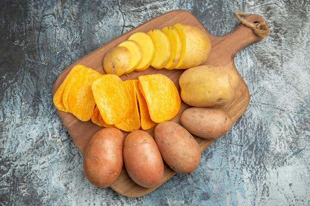 Boven weergave van knapperige chips en ongekookte aardappelen op houten snijplank op grijze tafel