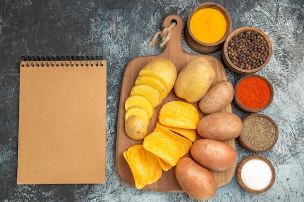 Boven weergave van knapperige chips en ongekookte aardappelen op houten snijplank verschillende kruiden en notebook op grijze tafel