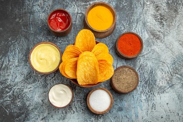 Boven weergave van knapperige chips op houten snijplank en verschillende kruiden op grijze tafel