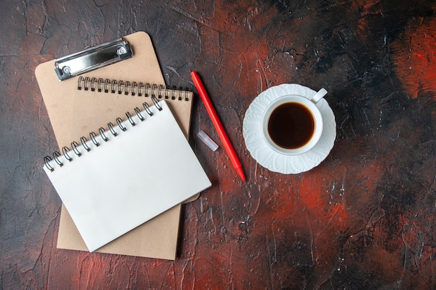 Boven weergave van kraft-spiraalnotitieboekjes met pen en een kopje thee op donkere achtergrond