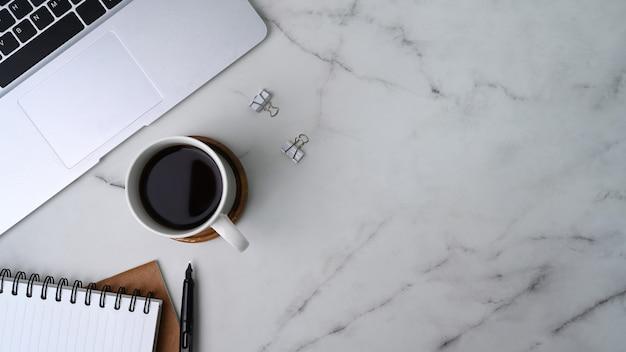 Boven weergave van laptopcomputer, koffiekopje en notebook op marmeren achtergrond.