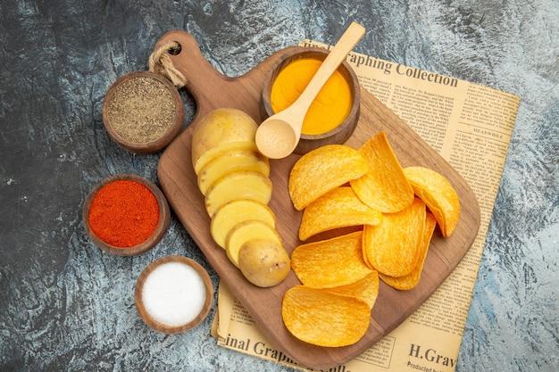 Boven weergave van lekkere zelfgemaakte chips gesneden aardappelschijfjes op houten snijplank en verschillende kruiden op krant op grijze tafel